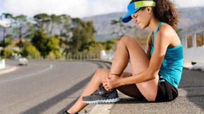 female athelete holding injured ankle 107814239